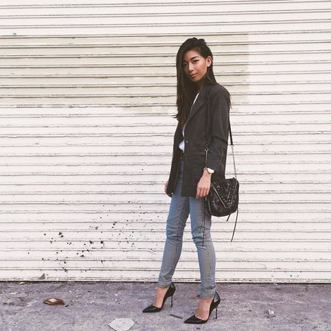 Black jacket with white blouse, gray jeans, and patent black pointed pumps