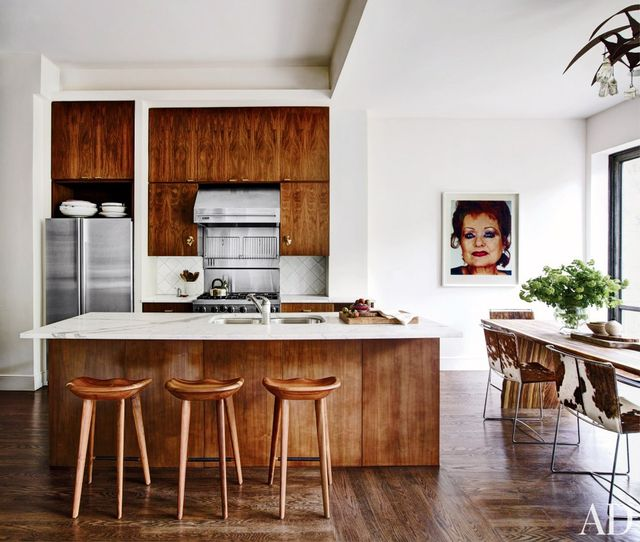 The addition of a slab of marble to the rich wooden island in this kitchen brightens its more rustic elements to make the space elegantly modern.