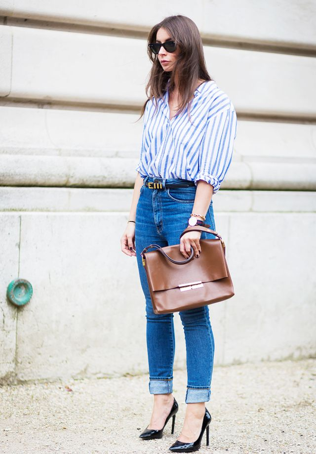 Every woman needs this uniform in her closet: a classic striped button-down blouse, high-waisted jeans, and black pumps.