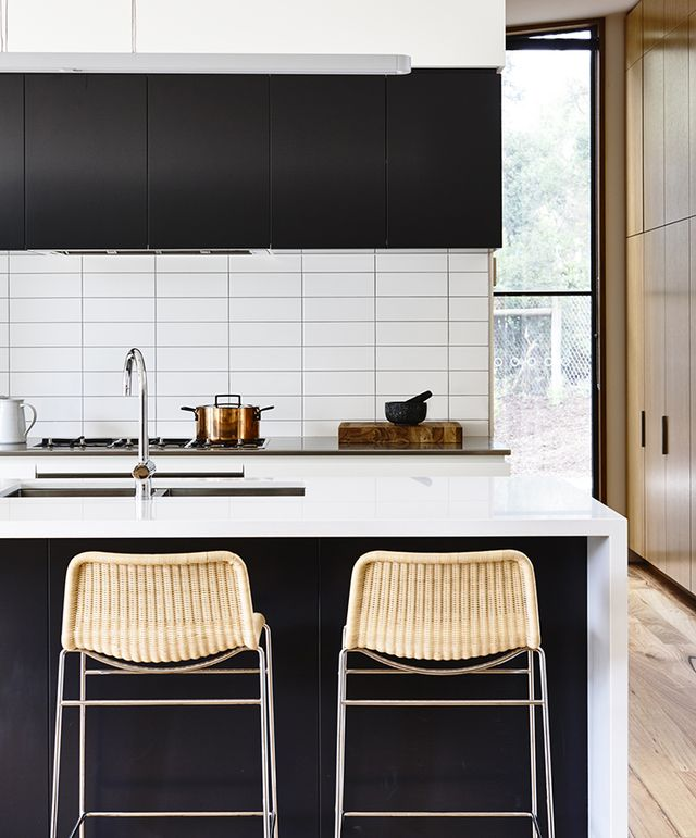 Black and white go modern in this kitchen with minimal cabinets and tile arranged in a grid pattern. Woven counter stools add some warmth to the contemporary space.