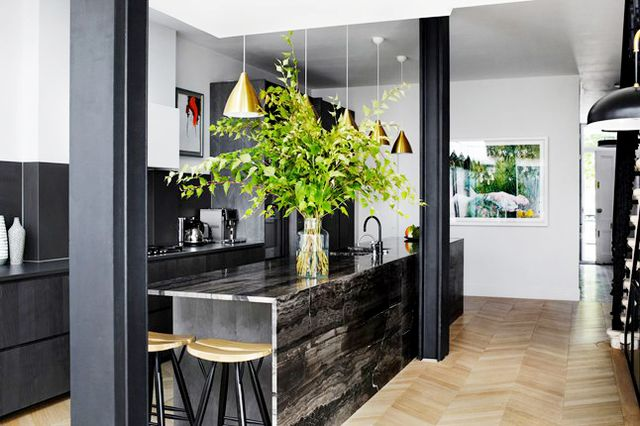 Combining black cabinets with black countertops could feel oppressive, but in this London townhouse designed by Suzy Hoodless, the kitchen feels welcoming and open thanks to warm brass pendant...