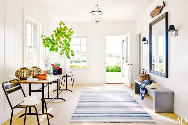 This cool coastal foyer projects a decidedly preppy vibe thanks to its large striped rug, classic light fixtures, and nautical details. A concrete bench and industrially influenced side chairs...