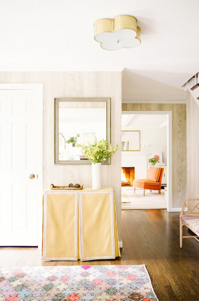 A traditional skirted console with contrast tape trim lend this entryway plenty of preppy appeal, but the brass quatrefoil light fixture adds yet another layer of classic interest.
