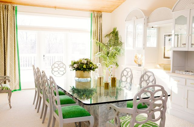 A set of classic Frances Elkins chairs upholstered in a saturated green color brings prepto this dining space. The drapery flaunts a subtle pattern with a contrast trim that coordinates with...