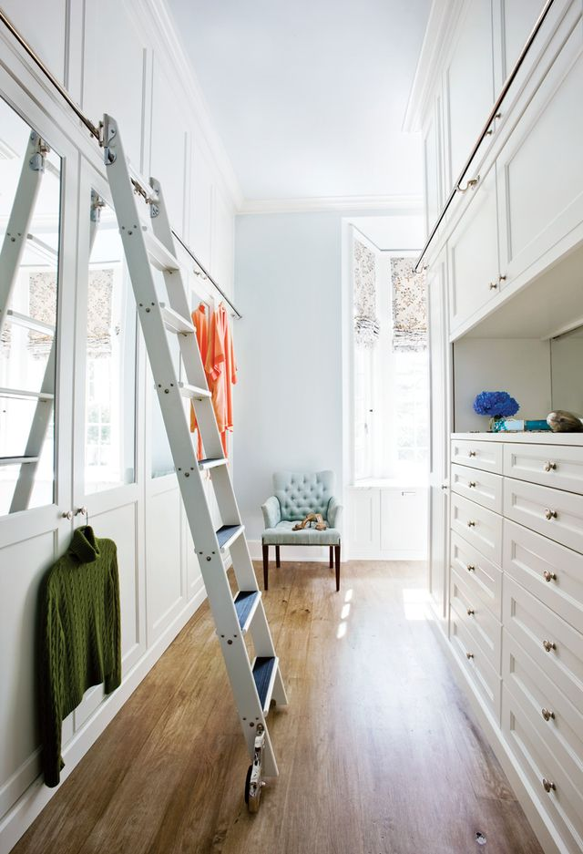 All of a sudden a small closet feels huge when you can swiftly reach things up high. We like the glamorous look of the brass ladder bar here, too.