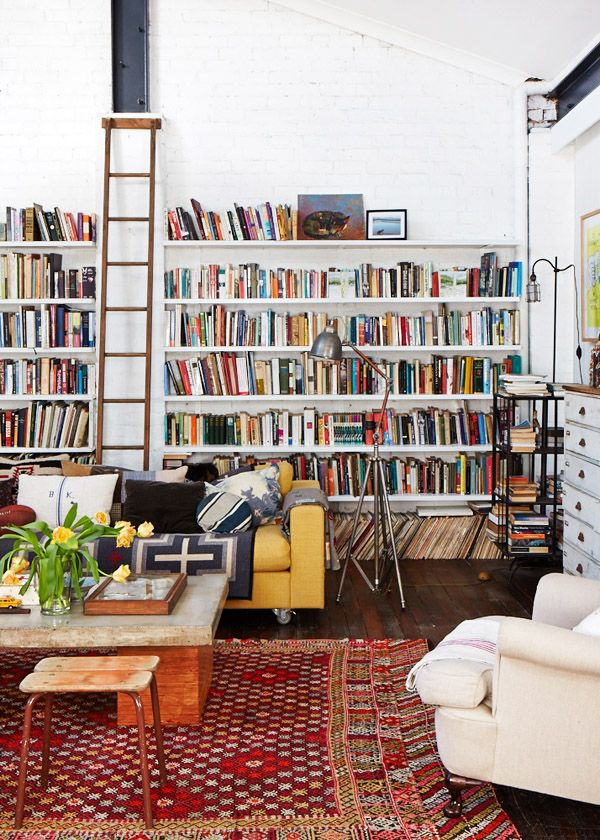 This ladder doesn't slide, but it's easy to move across the room's wide expanse of bookshelves.