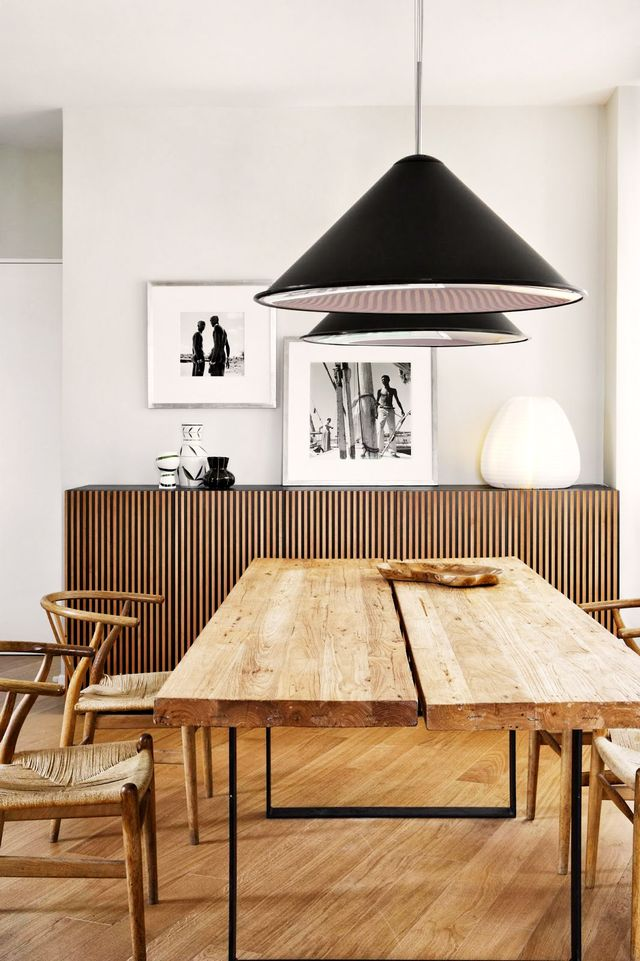 A sleek pair ofcone-shaped black pendants serves as a modern counterpart to a dining space composed of rustic, monochromatic wood tones.