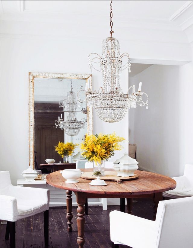 Hovering just above a round, rustic dining table, this sparkling chandelier adds irresistible beauty to the casual yet elegant space.
