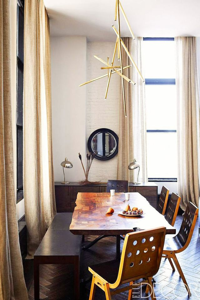 We love the inspired mix-and-match style of this dining space. The linear gold form of the chandelier adds a dash of artful polish to rougher-hewn pieces.