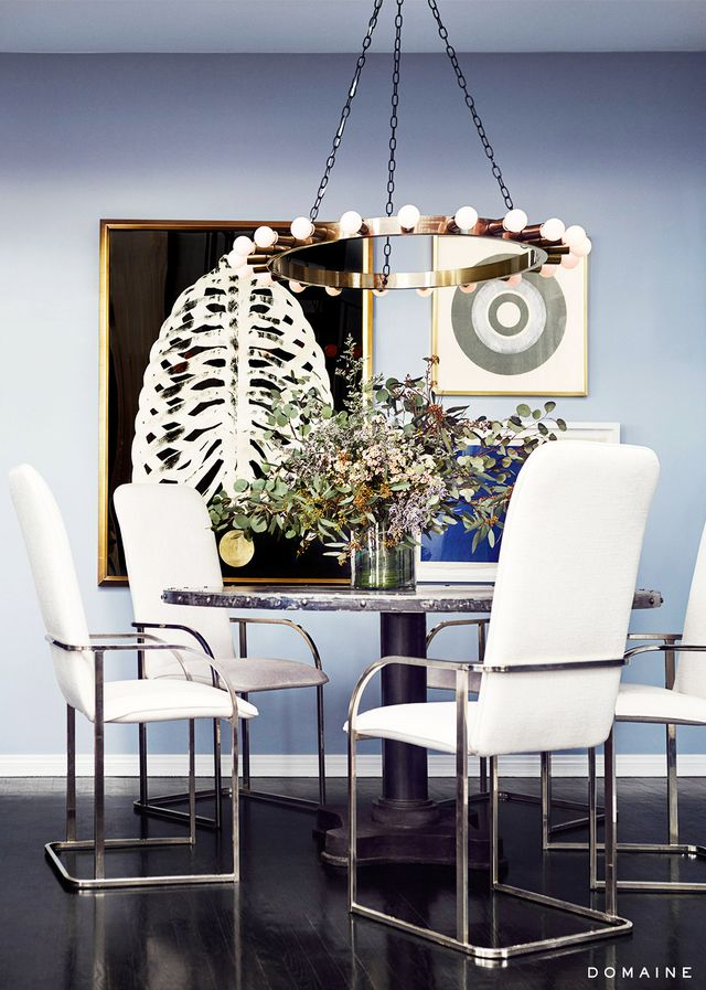 A glam-meets-industrial chandelier matches the edgy art arrangement and elegantly hard-edged furniture in this dining space.