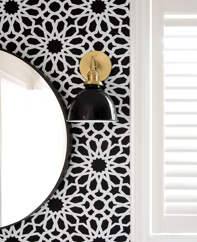"""One of the most statement-making elements is the F. Schumacher Agadir Screen Noir Wallpaper ($76/roll), which she hung on one wall. """"I knew I wanted to add one wall of bold wallpaper behind..."""