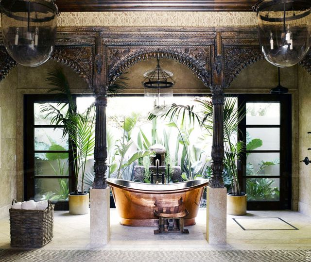 The copper Waterworks tub in this Martyn Lawrence Bullard–designed Malibu home feels practically like it's outdoors, sitting adjacent to big doors open wide to lush tropical plants.