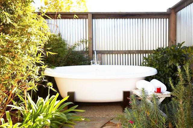 One of the cottages at The Carneros Inn in Napa Valley has its own private outdoor tub surrounded by beautiful landscaping and a cool galvanized fence. Simple but stylish.