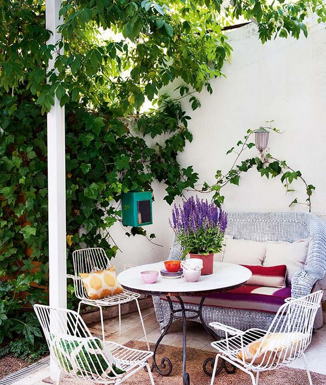 Plenty of color and thriving plants bring this outdoor dining space in Madrid to life.