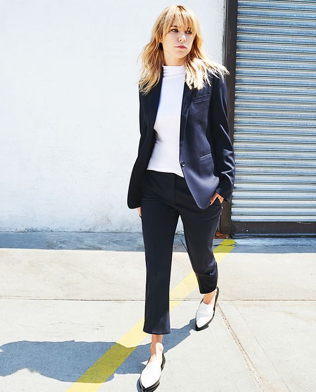 On Courtney Trop of Always Judging: The Kooples Timeless Suit Jacket ($470) in Black and Timeless Suit Trousers ($240) in Black; Theory Ribbed Viscose Cruzio Turtleneck ($140) in White; 10 Crosby...