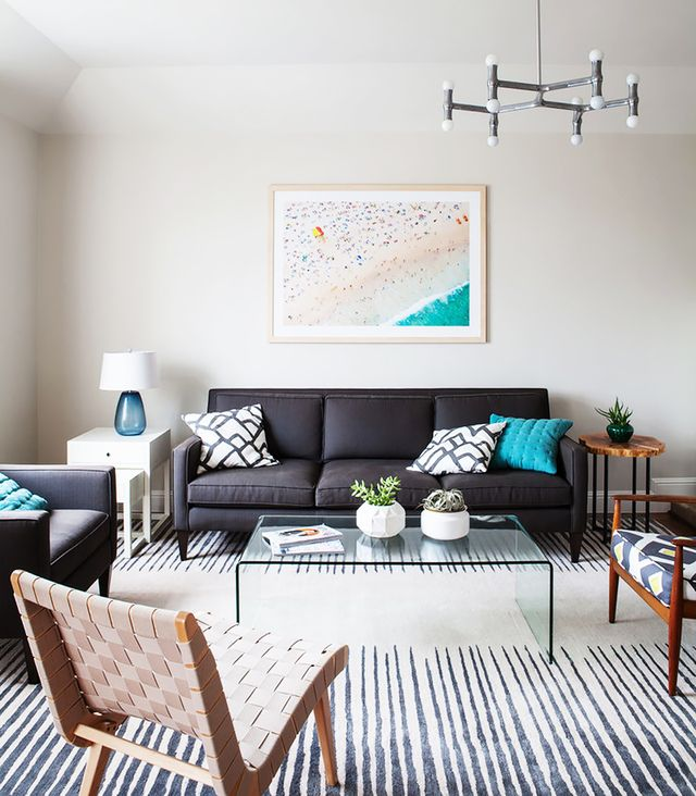 Sometimes all it takes is one regal rug to make a room stand out with pride and polish. The cute cushions on the sofa add the finishing touch.