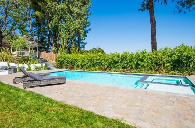 An entertainment-focused backyard includes a pool, spa, fire pit and bar with a built-in grill and an outdoor refrigerator.