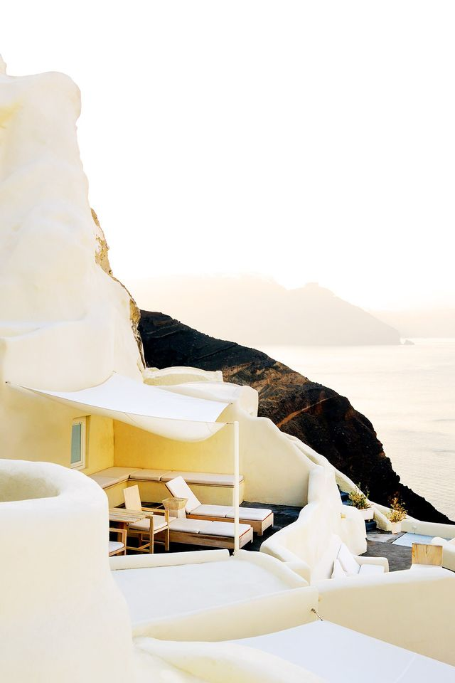 Overlooking the Aegean Sea, this cliff-top hotel shimmers in the late-evening wash of golden sunlight.  Location: Mystique Hotel Santorini, Santorini, Greece