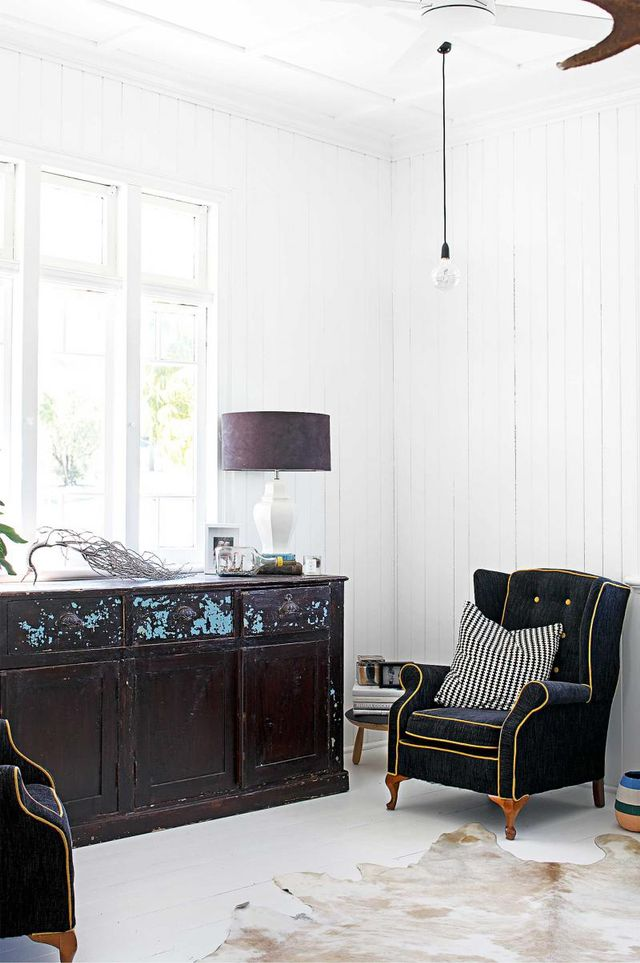 This room proves that white works with anything. The vintage cabinet sits casually beside the Victorian-inspired armchairs, with an industrial pendant lamp hanging overhead and a cowhide rug...