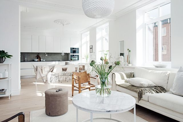 This spacious open-plan room is perfectly accented with warm tan tones and a touch of greenery to break up the white. Different variations of white color have been used...
