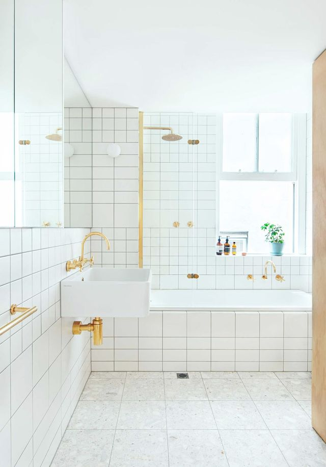 The variety of tile sizes add interest to this white bathroom, beautifully accented with gold hardware and plumbing.