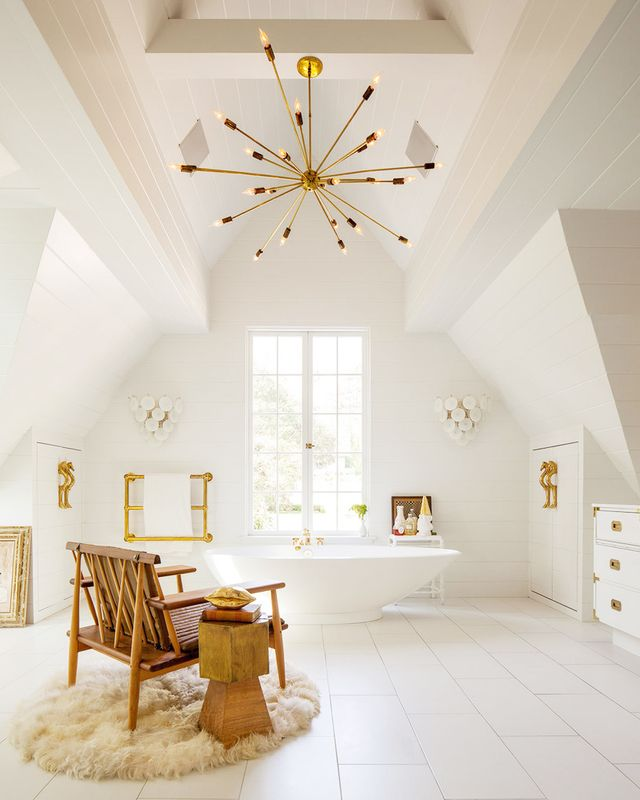 The only way to take a bath is surrounded by the bliss of all-white space, looking up at that beautiful brass chandelier. Take rest as the bath fills up in a tan chair complete with soft sheepskin...