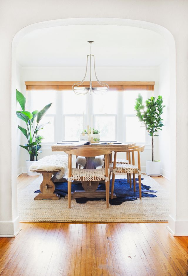 "This stark white space was given a ""half bungalow half fluffy minimalist"" vibe with wooden dining chairs and that amazing modern chandelier. The weaving and the rugs bring texture and color."