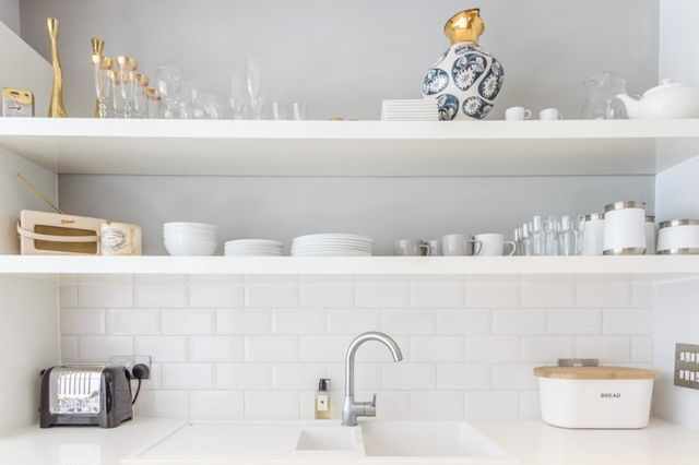 A blogger's charming London kitchen with white subway tile and dove gray make the perfect backdrop for a serene palette of dishware. Gleaming pops of gold up the luxe level.