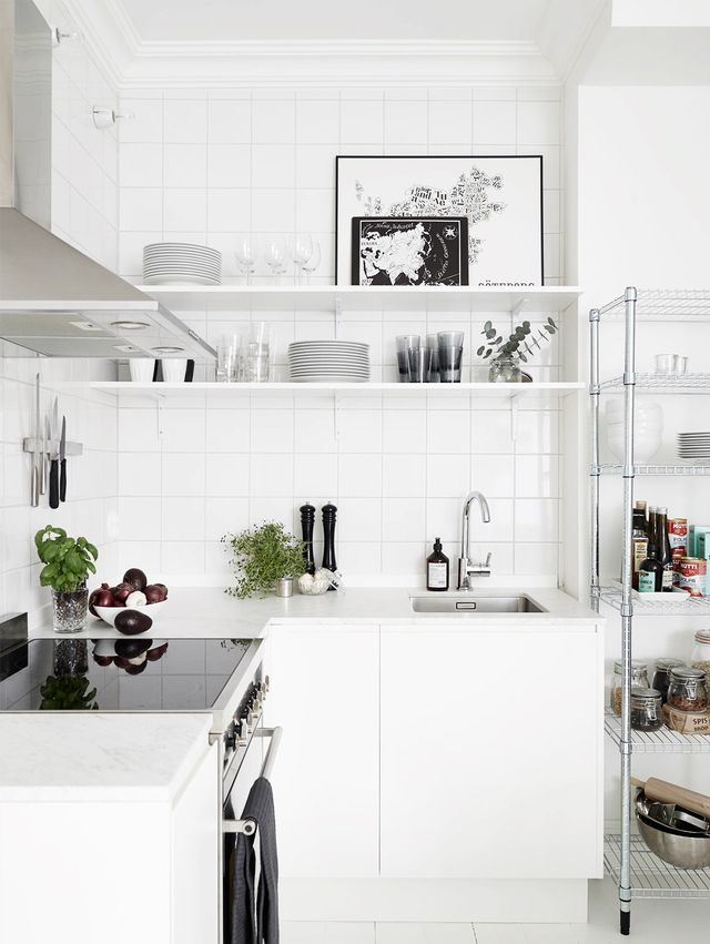 A small Swedish apartment's kitchen is stylishly minimalist, thanks to a neat black-and-white palette of kitchen necessities on display.
