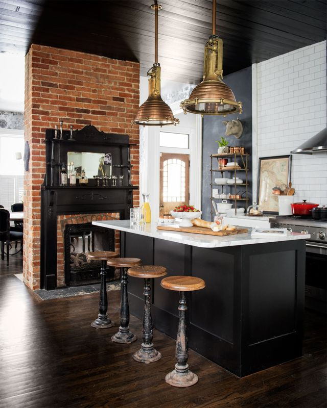We love the industrial vibe of this kitchen. The impressive metal pendant lights stand out against the dark ceiling, and the wood stools add the perfect warm accent.