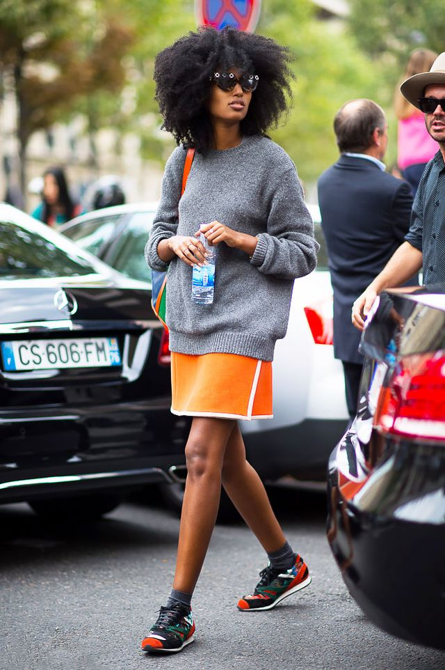Embrace the sporty trend and style your knit with a bright mini skirt and colorful sneakers.